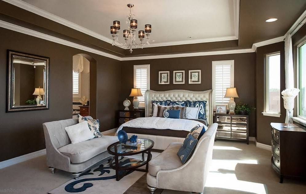 Master Bedroom Layout With Sitting Area And Brown Walls With White Border Trims And Chandelier