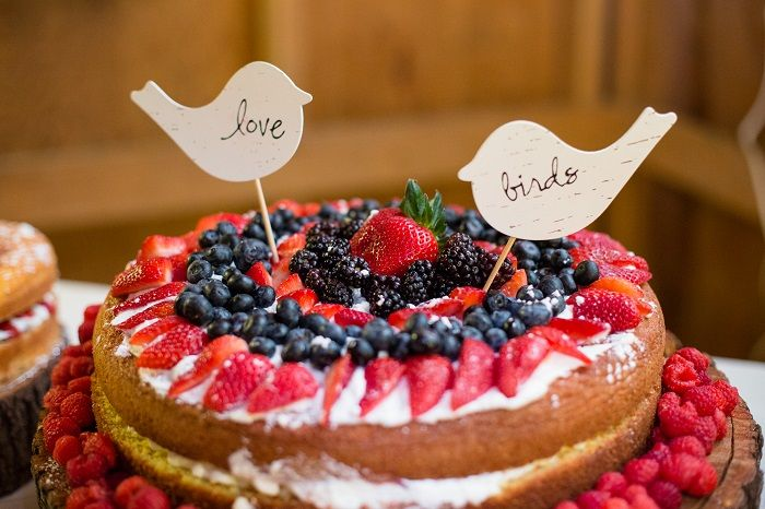 Naked wedding cake with tons of berries, topped with homemade birch wood love birds | fabmood.com