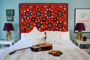 21 Creative Alternatives to a Conventional Headboard: Hang a quilt or tapestry in place of a headboard.