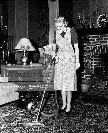 1930s 1940s Woman Housewife Wearing Apron Pushing Electric