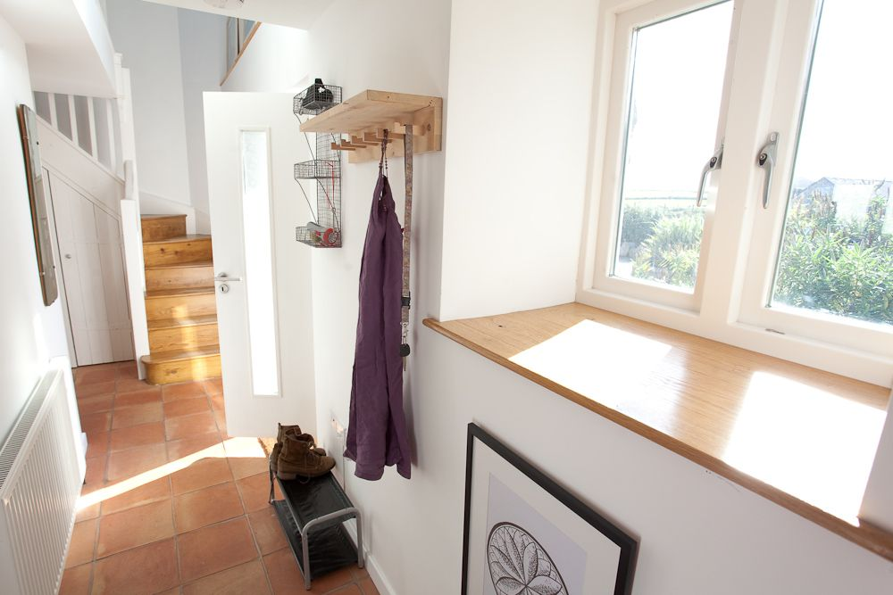 Light and airy hallway. NB stairs  flooring  wooden window sill.  This type of plain white ballustrade looks good here