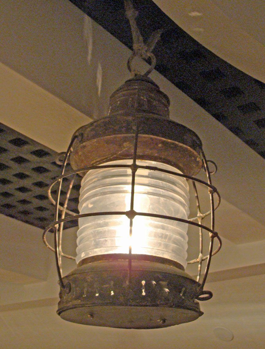 An Authentic Antique Marine Brass Anchor Lantern Hangs Lighting Up A Cabin Below Deck Of