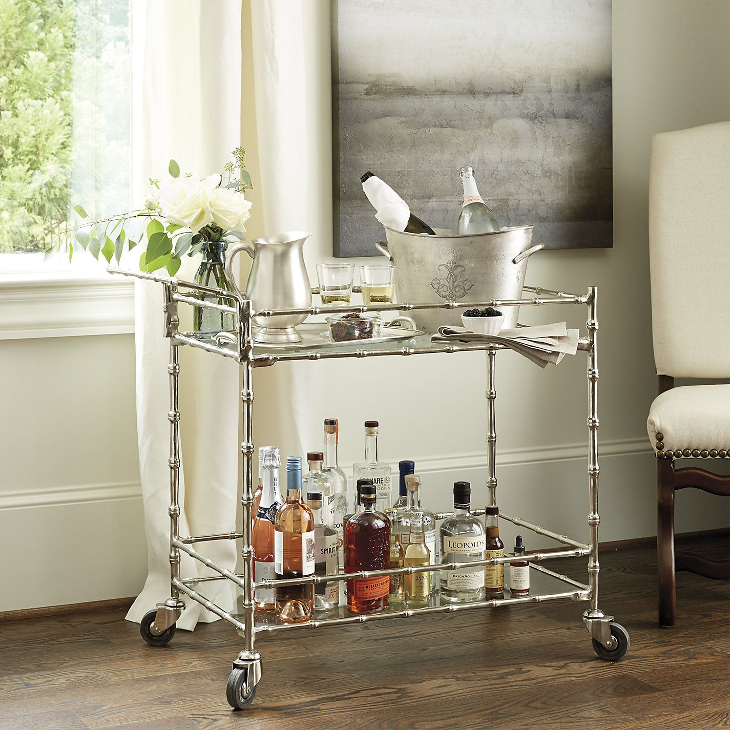 With this bamboo-style bar cart, the drinks can follow the party. Two tempered glass shelves with gallery rails keep barware and bottles corralled and ready for serving.
