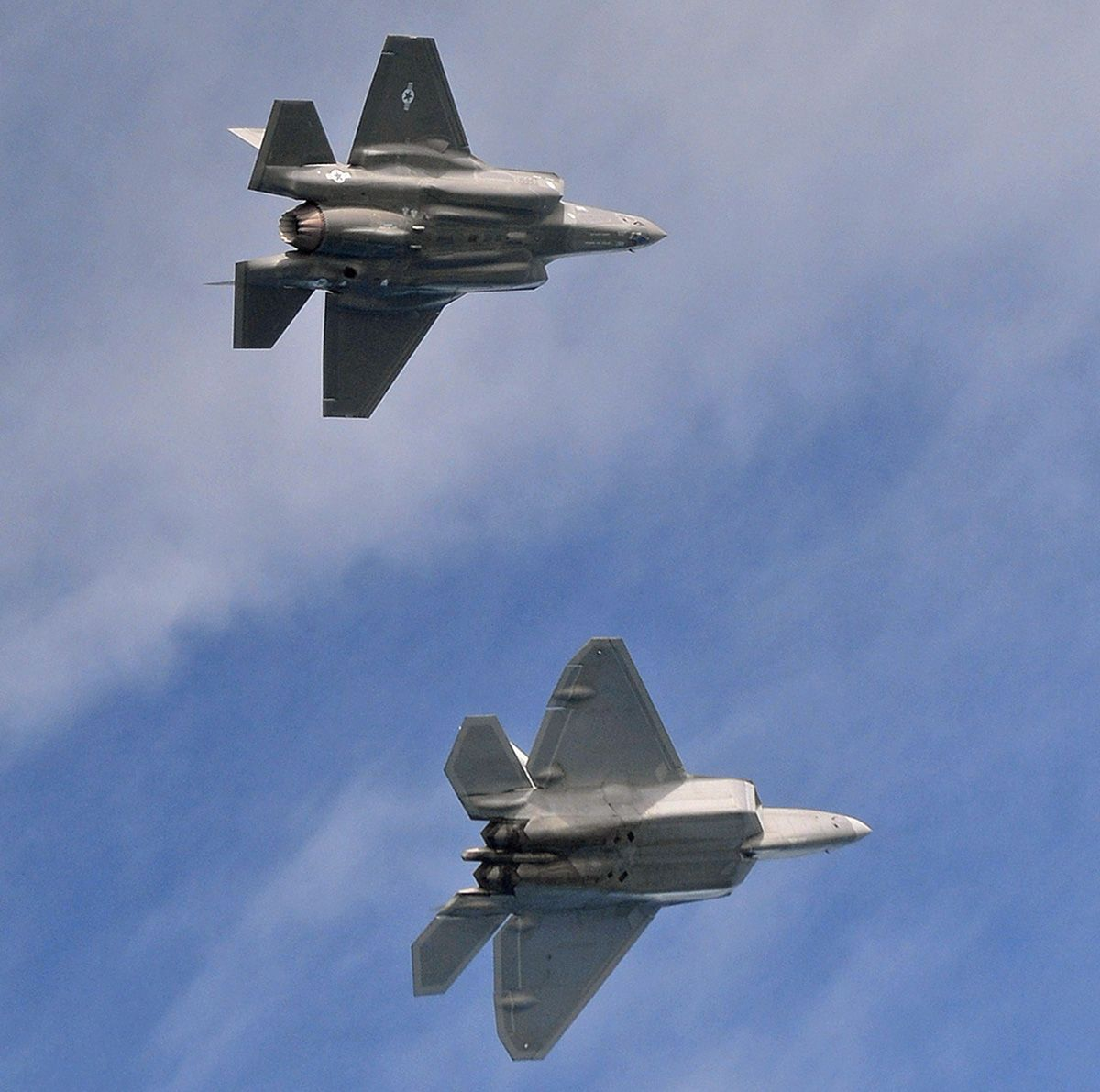 The underside of the F-22 is much flatter than that of an F-35.  Photo by MSgt. Shane A. Cuomo