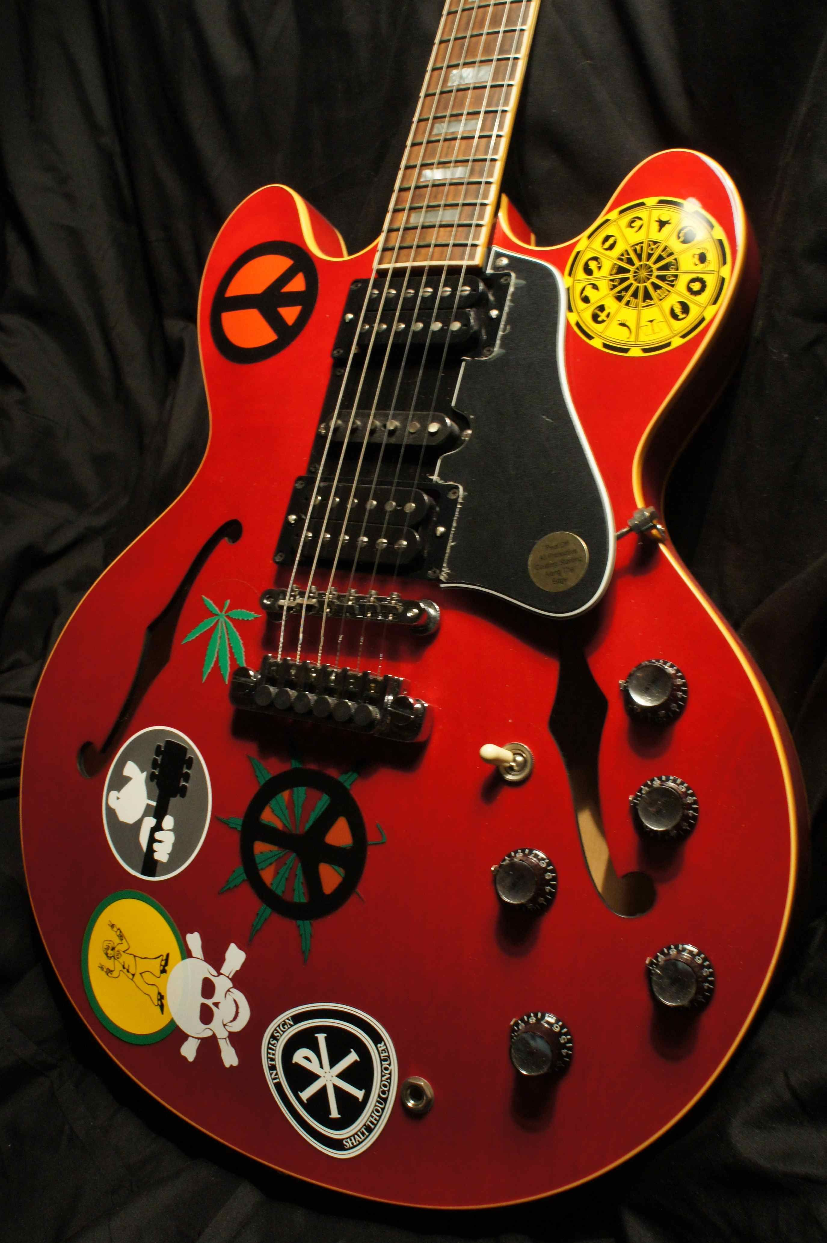 """Gibson Alvin Lee """"Big Red"""" ES 335. A replica of the famous """"Big Red"""" ES 335, full of stickers, played by Alvin Lee of Ten Years After (as seen in Woodstock!). Alvin liked the sound of Strats but was not confortable with the dimension of the guitar and volume knobs placement. So he installed on a piece of plastic the bridge pickup of the strat in the mid of the Es335, added a volume pot and connected it to the output (so you can never switch it off, just pull down volume)."""