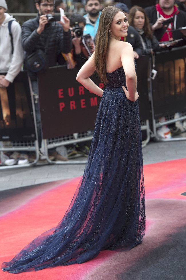 """Elizabeth Olsen attends the premiere of """"Godzilla"""" in London in an Elie Saab navy strapless couture gown from the Fall 2013 couture collection accessorized with Louboutin shoes, and Piaget earrings and ring."""