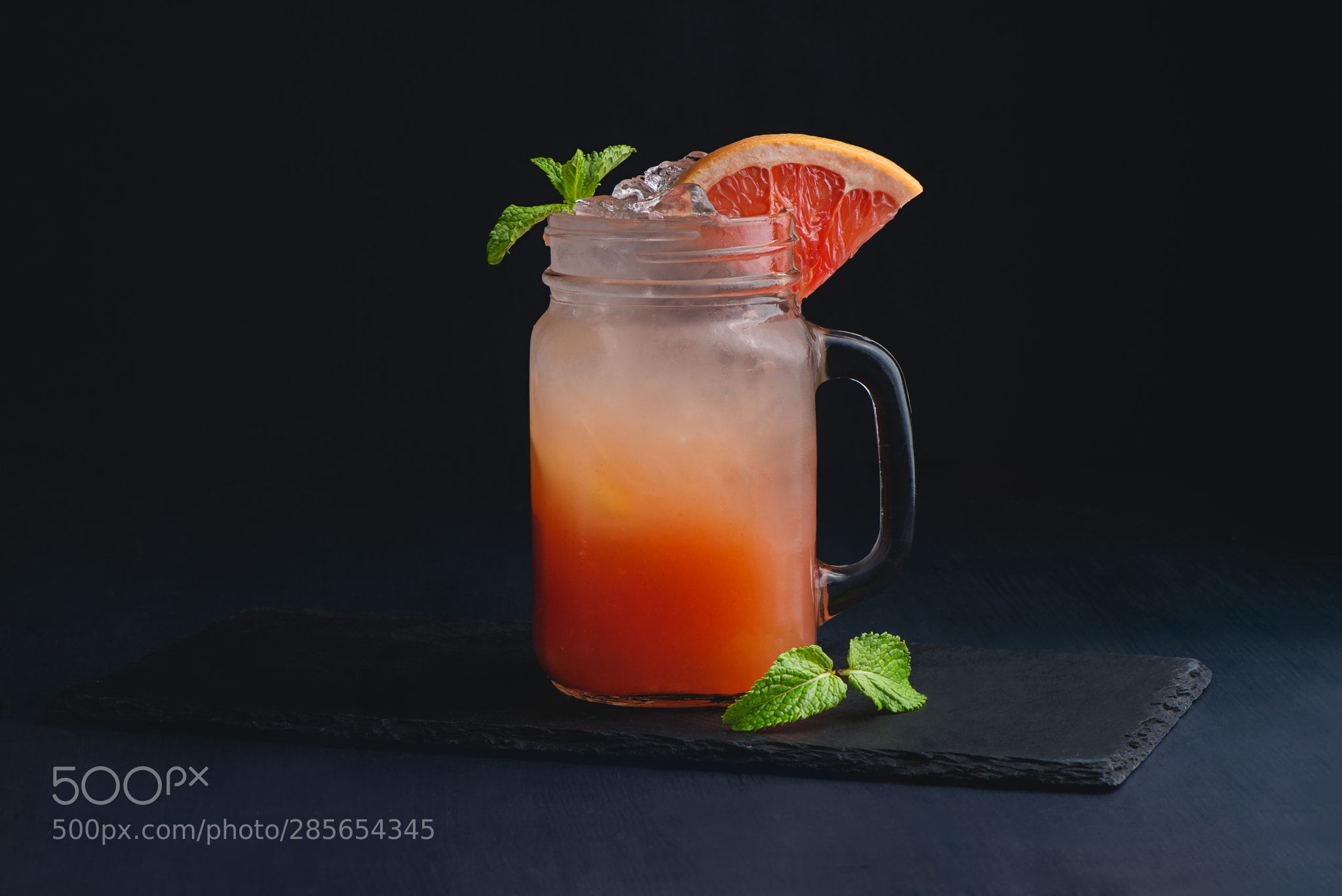 Ice cold citrus cocktail in a vintage glass mason jar