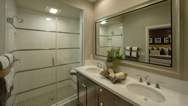 The Bungalow 7 #master #bathroom features glossy double sinks and an enclosed commode.