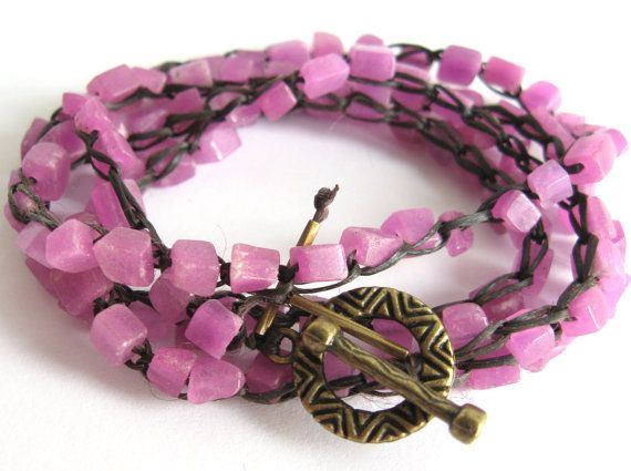 $24.99 Deep pink pebbles of New Jade (a form of serpentine) in this bracelet are crocheted onto a faux sinew polyester cording and finished with an antiqued gold-plated toggle clasp.