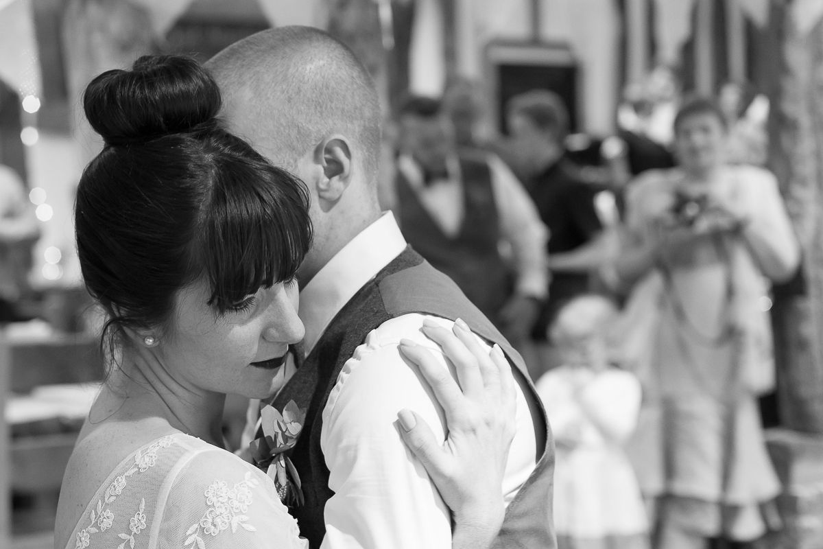 The bride & groom enjoy their first dance whilst some of their guests look on at Jimmy's Farm, Suffolk. www.headoverheelsphotography.co.uk