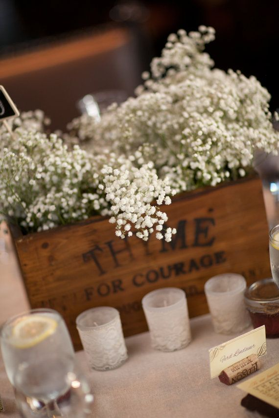Lace covered candles with babies breath. Could also be inverted: One hurricane candle with lace covering and babies breath wrapped around the bottom
