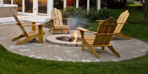 paver patio design with round fire pit and adirondack chairs
