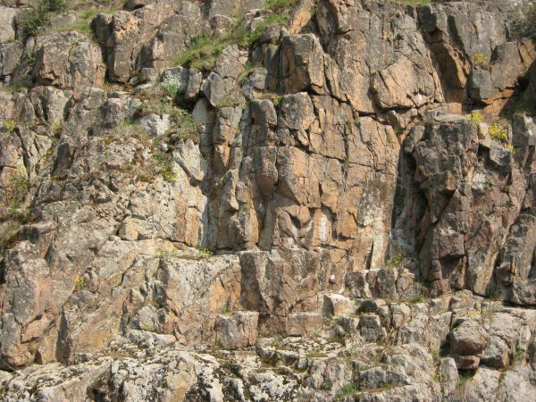 Rock cliff texture in brown and grey tones consisting of jagged