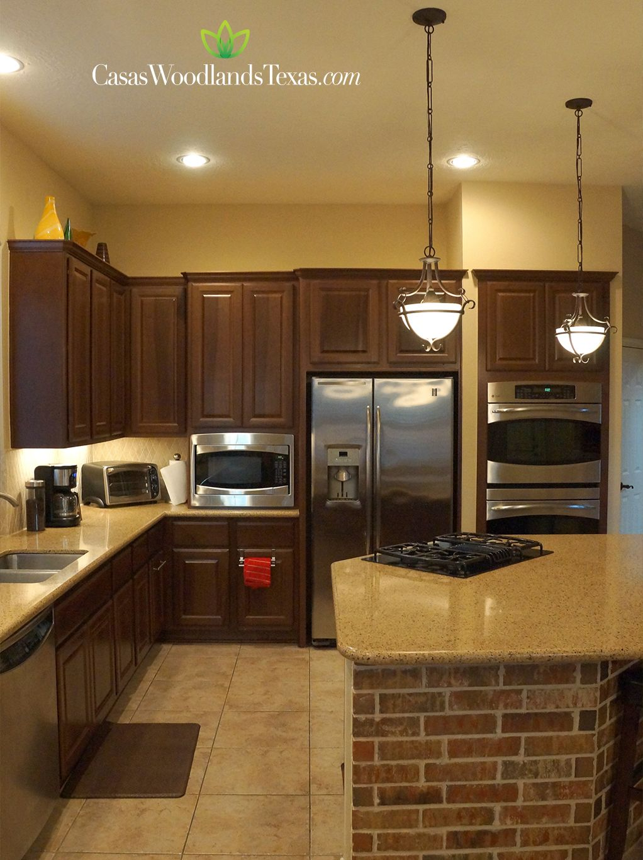La cocina cuenta con gabinetes de madera, encimeras de granito y ...