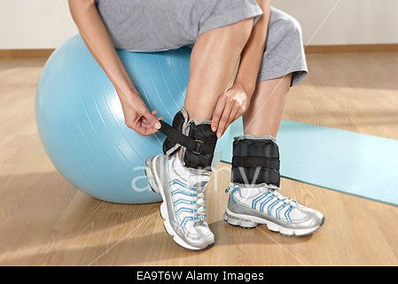 Woman applying weights to the foot links Stock Photo