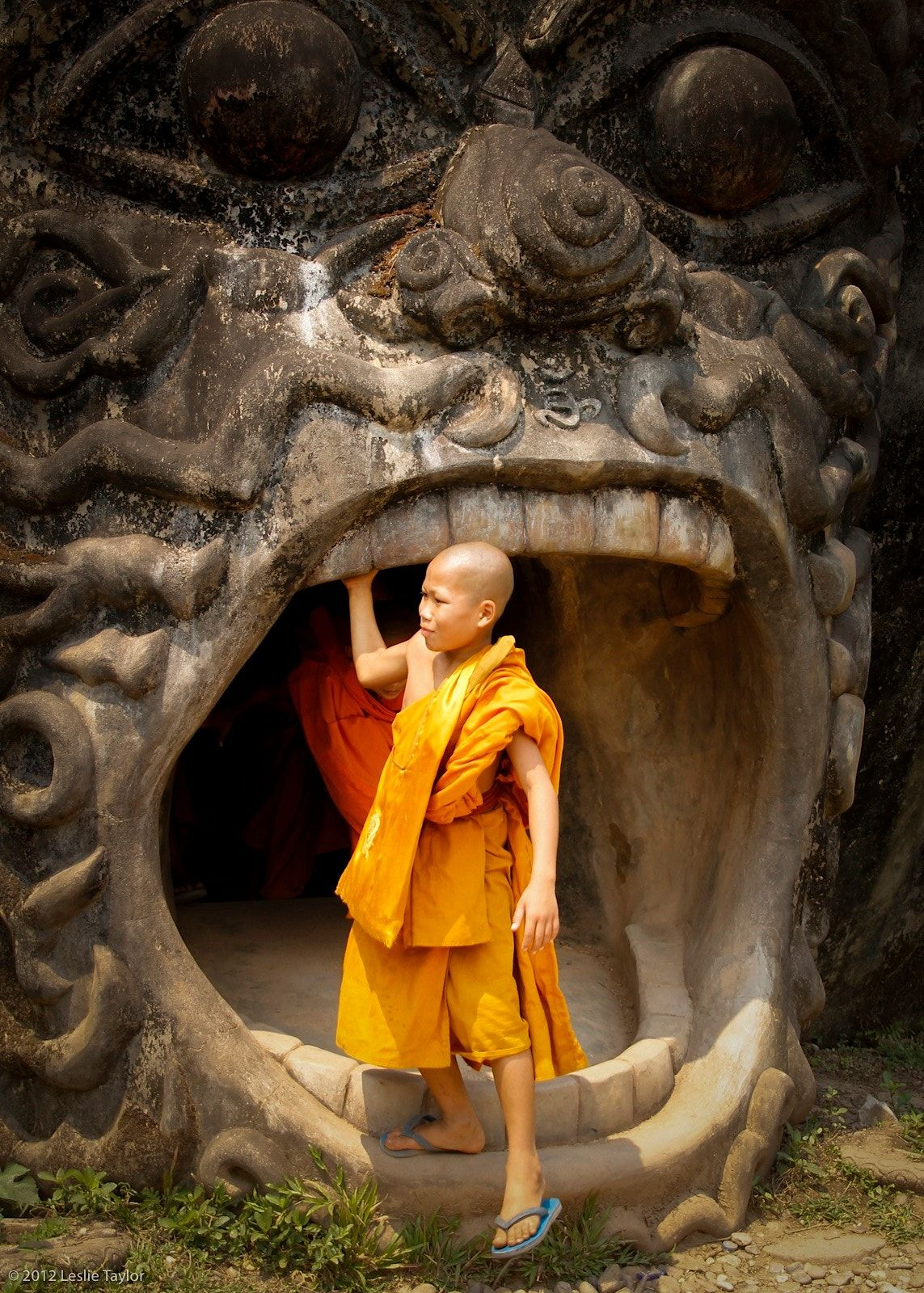 YOUNG LAOTIAN MONK - This shot was taken at the Buddha Park outside of Vientiane,  Laos. It was a Buddhist holiday and three young monks were visiting with their teacher.  They  had climbed to the top of this particular stone Buddha and I waited for them to come down through the mouth.