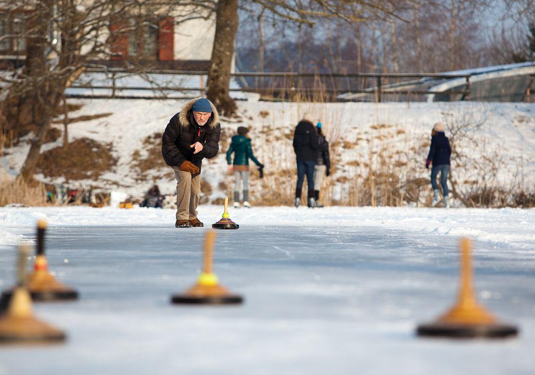 """Eisstockschütze auf dem Maisinger See.  Das Stockschießen ist ein alter Volkssport, der vor allem im Alpenraum ausgeführt wird. Ähnlich wie beim Curling ist es Aufgabe, den Stock möglichst nahe an das Ziel, die """"Daube"""", zu schießen."""