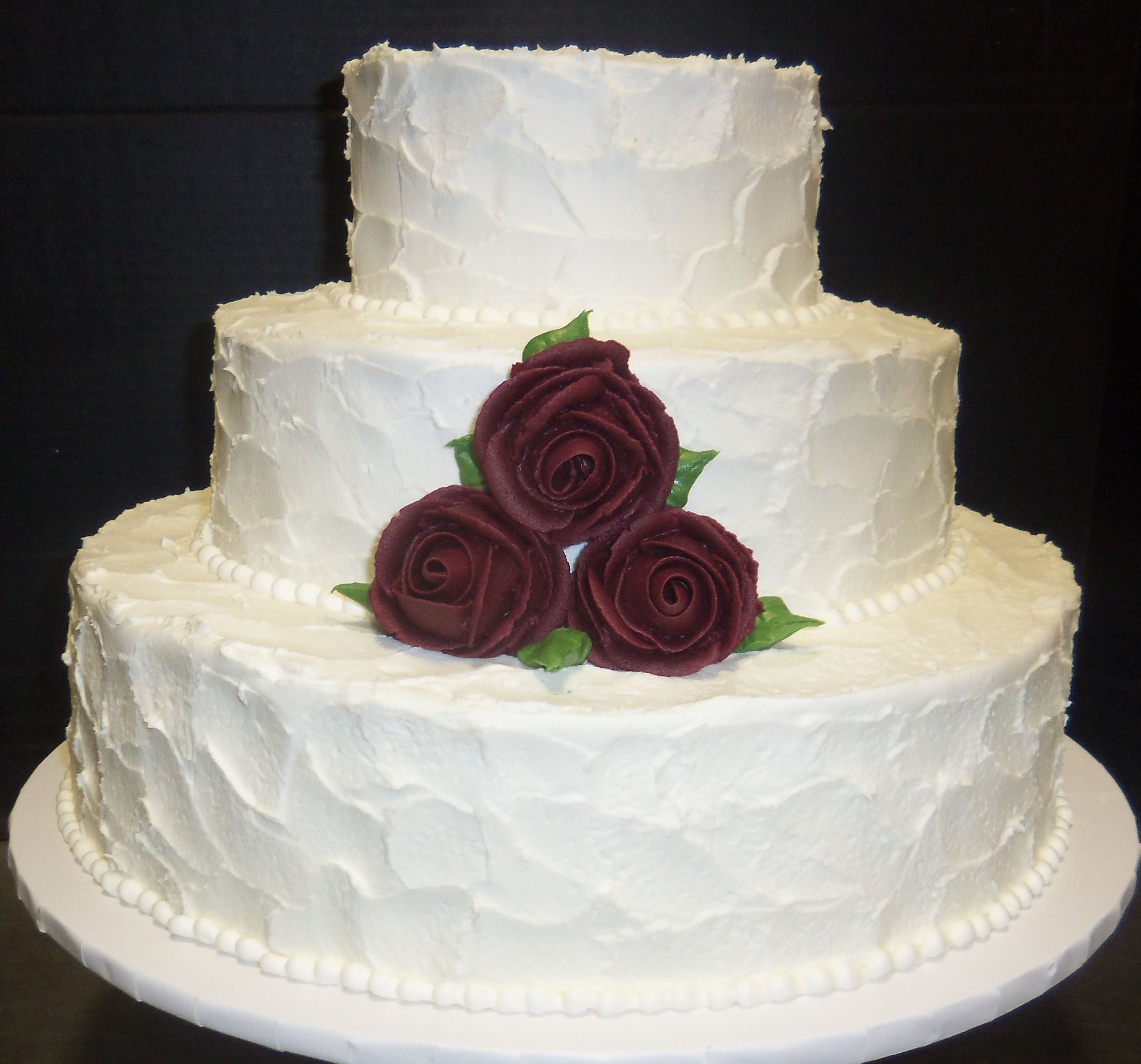 Deep red roses are featured on our white buttercream iced cake ...