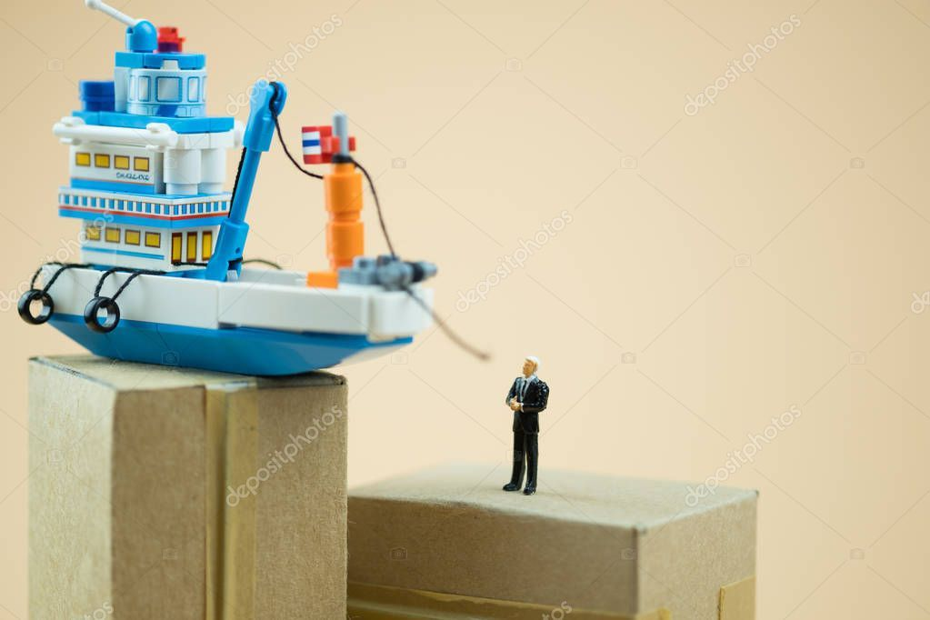 Miniature people businessman with boat Concept of ship cargo delivery or boat s