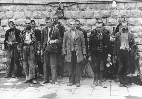 """Mauthausen, Austria, New prisoners who arrived at the camp, 1943-1944.  A group of 11 new inmates, standing near the """"Klagemauer"""", after a long journey to the camp in open train cars."""