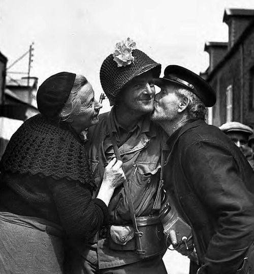 A GI from Des Moines receives a kiss of welcome from an elderly French couple after American troops liberated their town of St. Sauvuer in August 1944 (WW2)