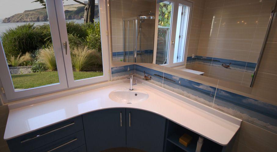 Un meuble d\u0027angle de salle de bain avec un plan de toilette résine galbé
