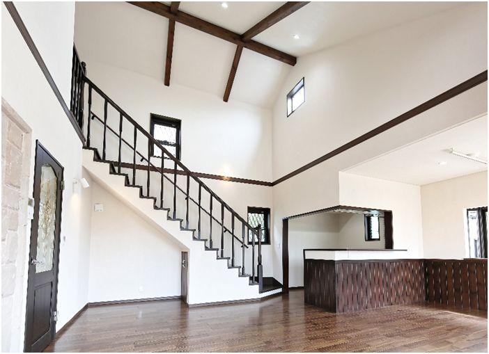 吹き抜の天井にはウォルナット色に塗装した化粧梁 白くて明るい空間を