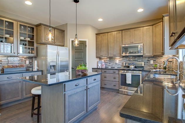 The Gray Cabinets Complemented By An Exciting Tile Backsplash Makes This Kitchen One To Remember Seen In The Redfield At Town Log Home Kitchens New Homes Home