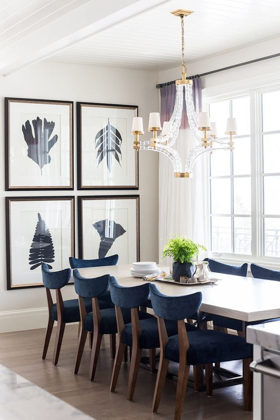 Accented With A Crystal And Brass Chandelier Large Cube Illuminating White Dining Table Lined Navy Blue Velvet Chairs
