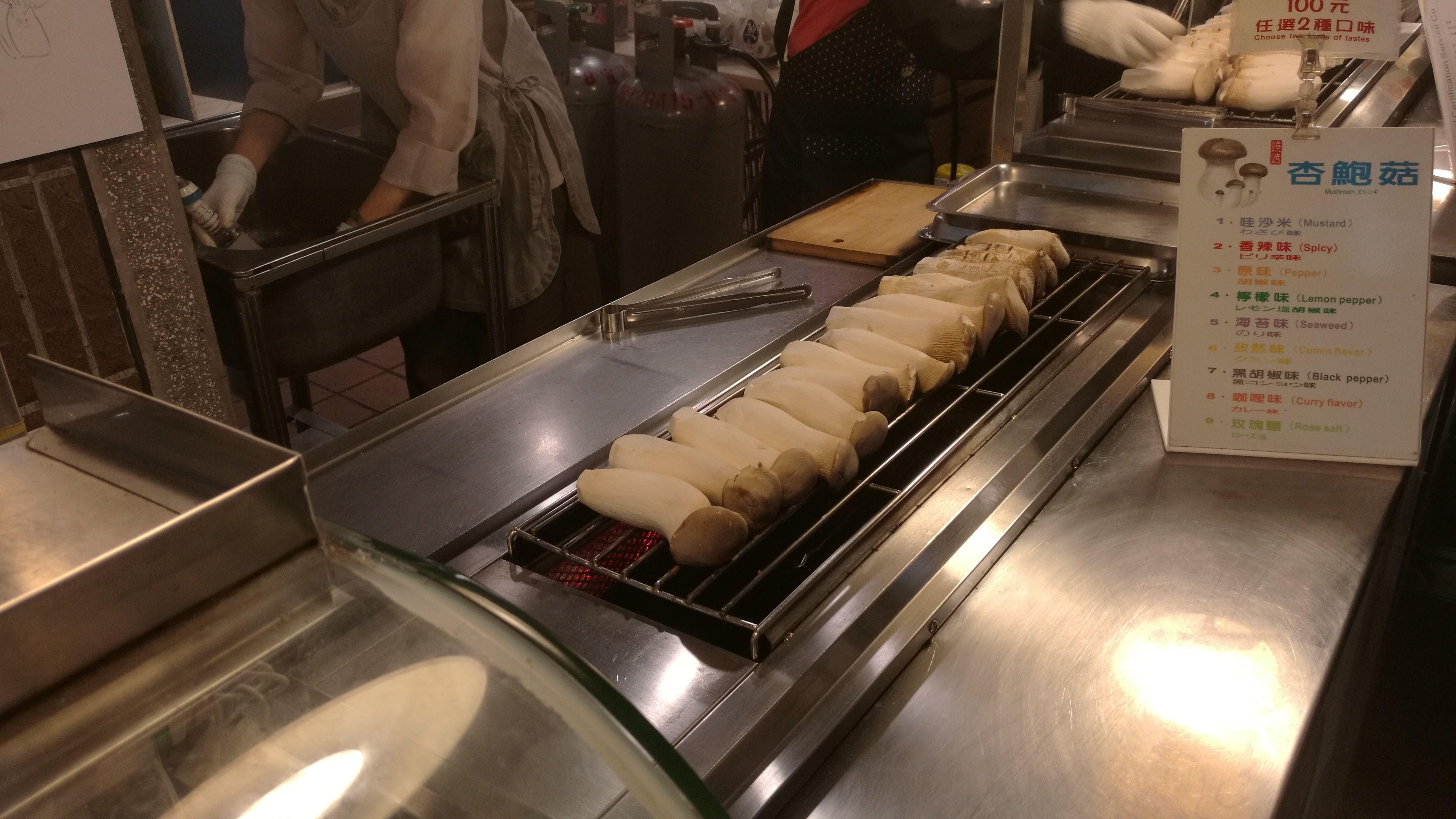 Preparando setas a la brasa con picante y lima en un mercado nocturno