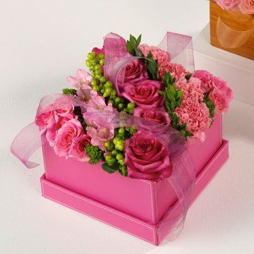 Pretty pink flowers in a square pink box, finished off with ...