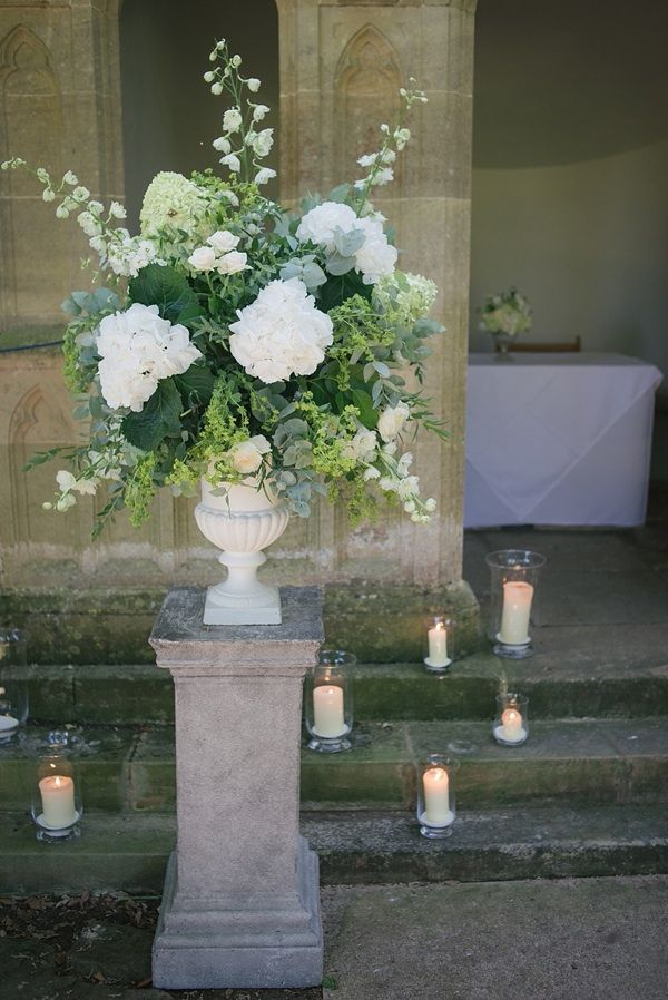 Melani and Matthew had pillar candles and tea lights in glass vases at the front of the aisle on the steps of the summer house to help creat...