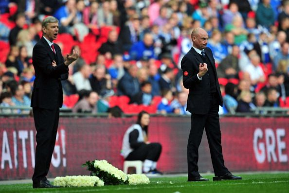 Wigan Athletic's German manager Uwe Rosler (R) and Arsenal's French manager Arsene Wenger gesture from the touchline during the English FA Cup Semi-final match between Wigan Athletic and Arsenal at Wembley Stadium in London on April 12, 2014.