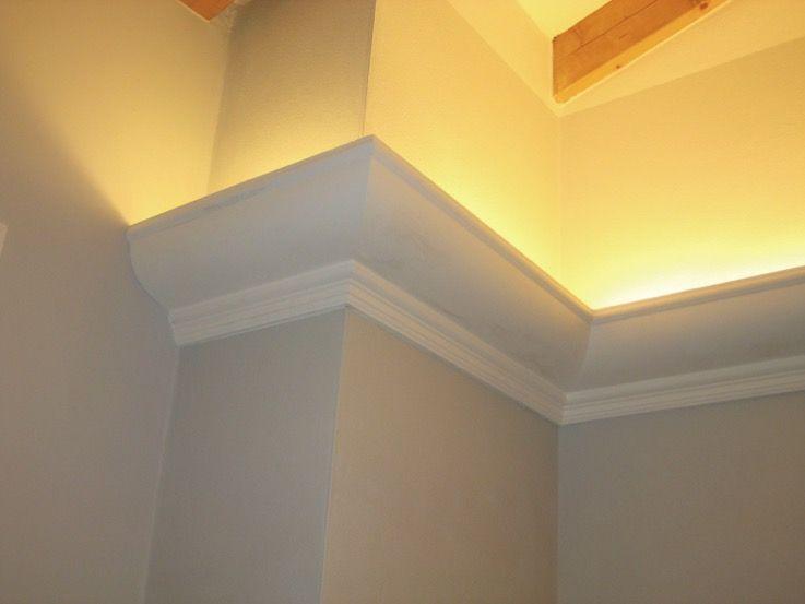 Cornice in gesso a lumiera posizionata su soffitto con travi in