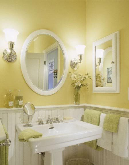 A Lovely Pale Yellow Bathroom With Bead Board And A White Pedestal Sink.