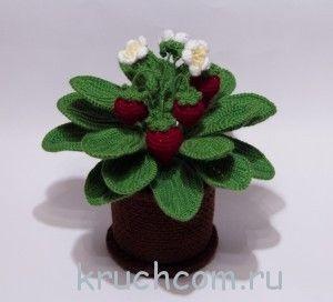 Crocheted flowers in a pot hook. Strawberries
