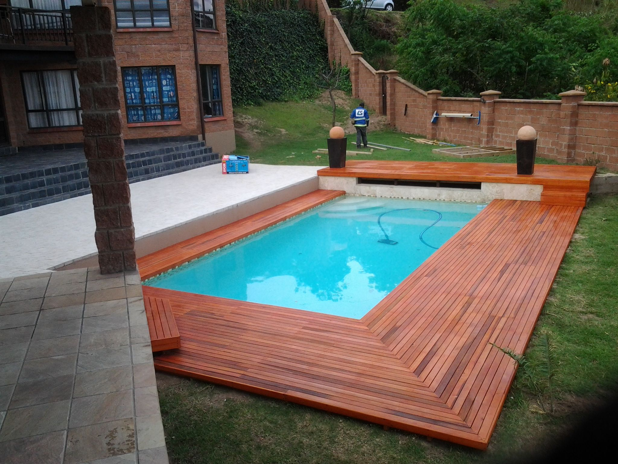 the idea here was to build a wooden sun deck that extended from the slasto of the pool area to meet the far side of the house