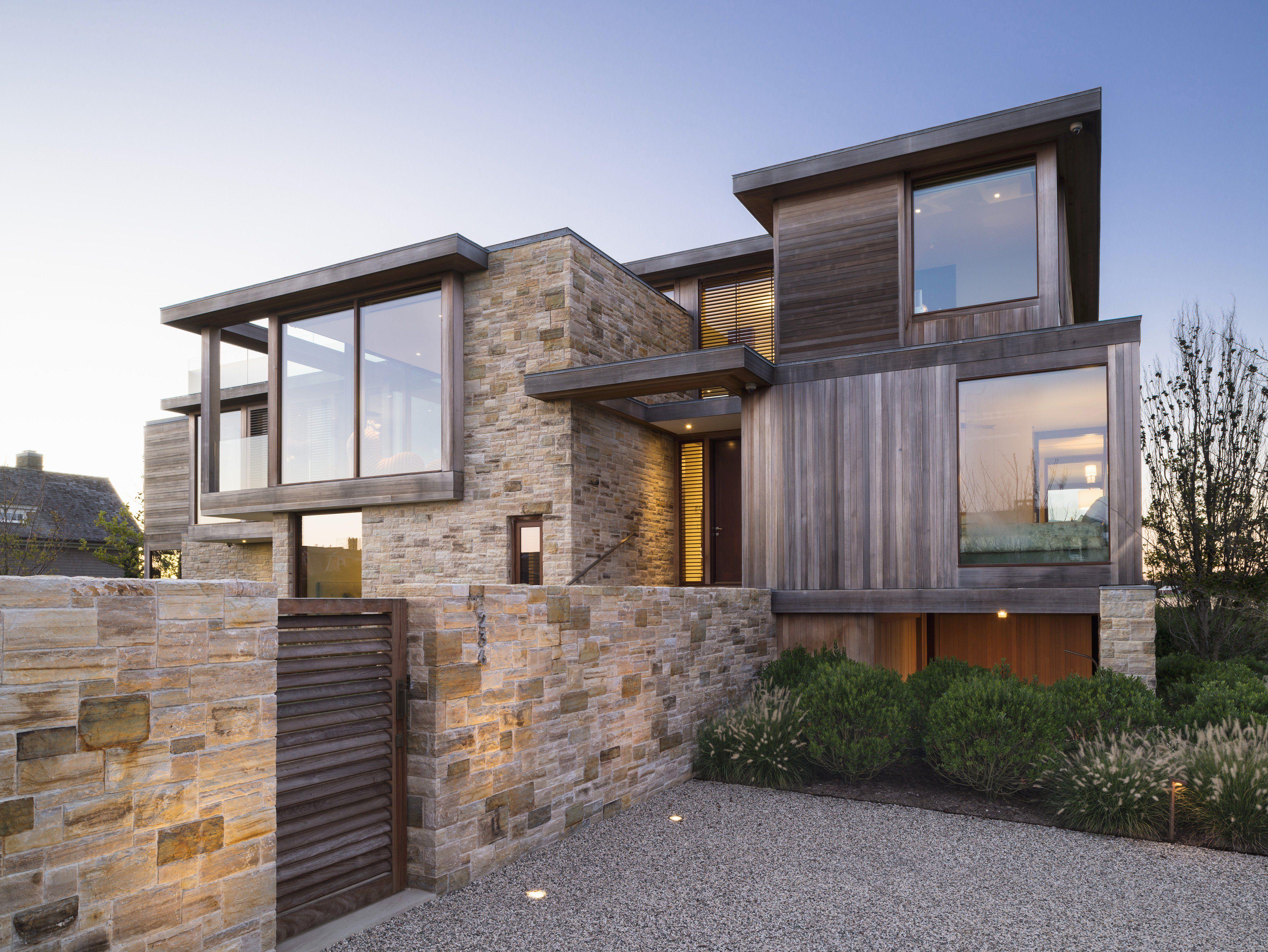 Ein Haus mit verschachtelter Fassade aus Stein, Holz und