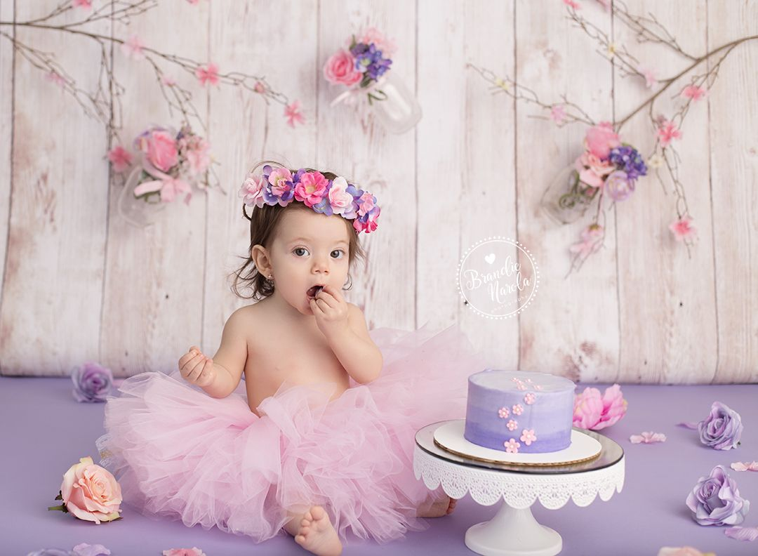 baby wearing pink tutu and flower crown for themed baby cake smash
