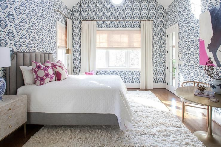 Restful blue and gray girl's bedroom is clad in Thibaut Thai Ikat Wallpaper and features a gray art deco headboard complementing a gray bed dressed in white bedding topped with pink geometric pillows.