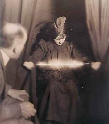 Eva Carrière photographed supposedly with a light manifestation between her hands and a materialization on her head.
