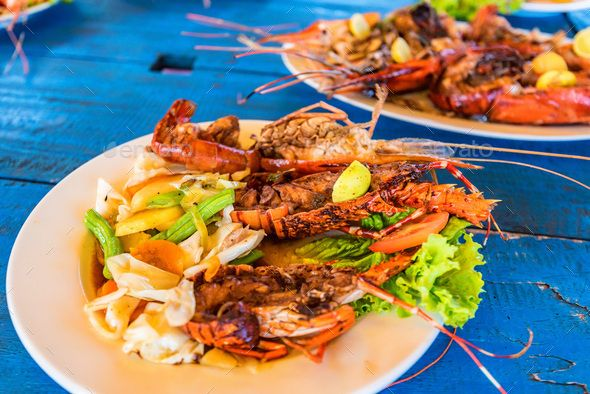 Tasty prepared lobsters and jumbo shrimps by Yakov_Oskanov. Tasty lobsters and jumbo prawns prepared with garlic and lime on tropical background. Traditional Lankan cuisine. #AD #shrimps, #Yakov_Oskanov, #prawns, #jumbo