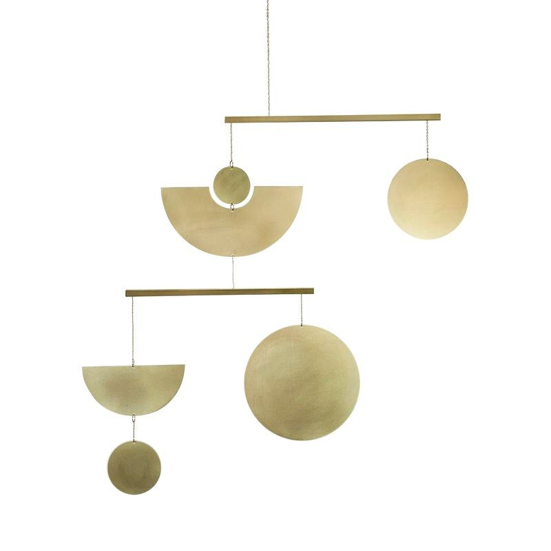 The mobiles are handmade in Austin Texas by designer Corie Humble. They are made from solid brass, a natural material that patinas with age. For design inspiration the mobiles play with geometric shapes to create a minimal design aesthetic. The mobiles are designed for any contemporary home. The mobiles would also be a lovely addition to a modern nursery.