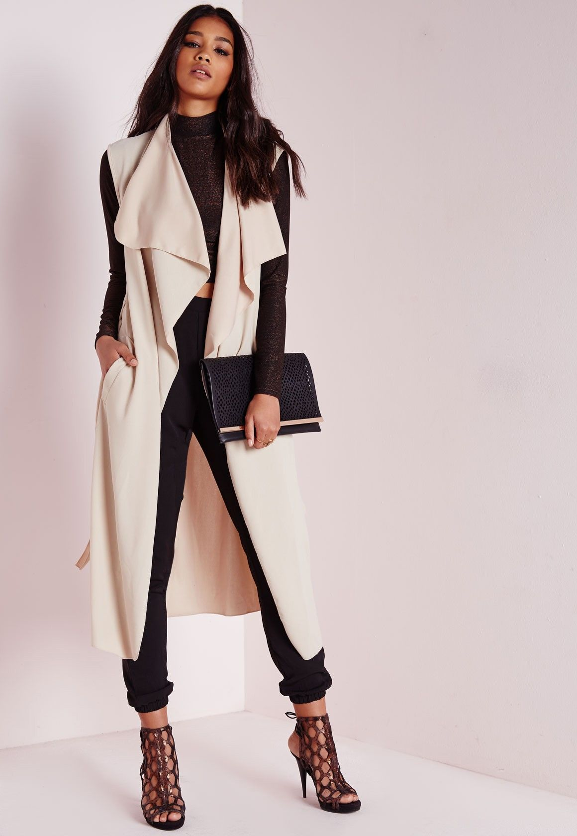 Define elegance in this chic camel waterfall duster coat. This belted  sleeveless beauty flows fluidly