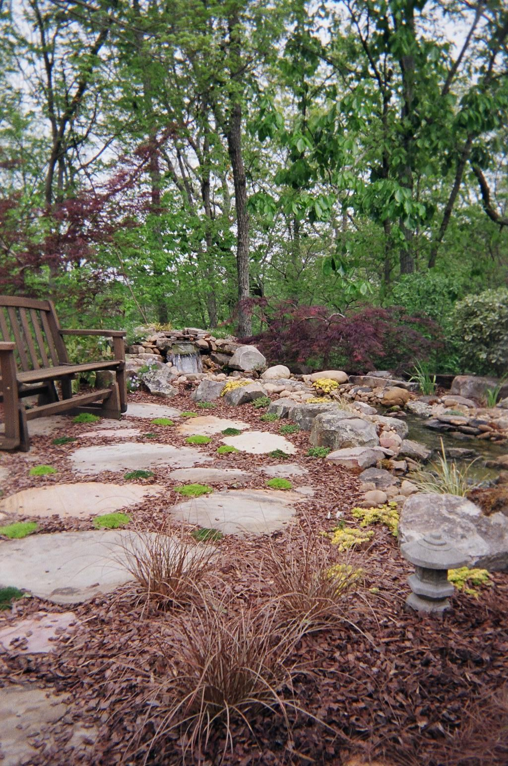 Rock patio with perennial planting, water feature and full ...