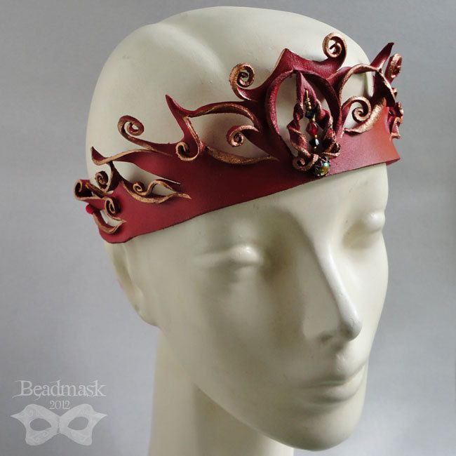 This sculpted leather crown or tiara was hand cut and shaped from fine tooling leather. It is dyed and painted in rich crimson with bronze accents. At the center is a vintage glass cabochon, which is accented with glass beads and Swarovski crystal. etsy.