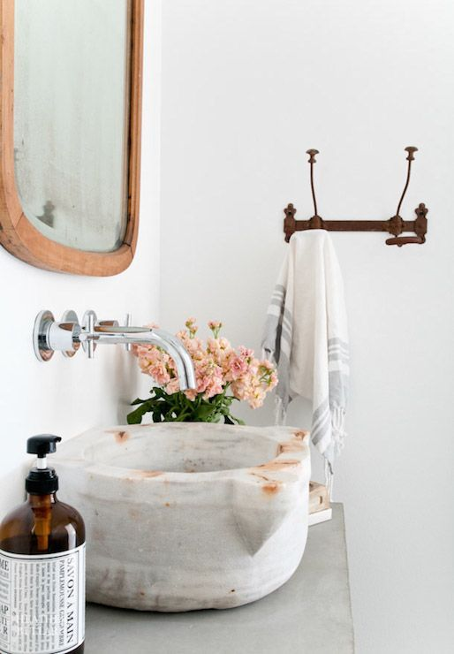 A marble sink adds a luxurious touch to a white bathroom. Brighten up the space using pink peonies and wooden detailing.