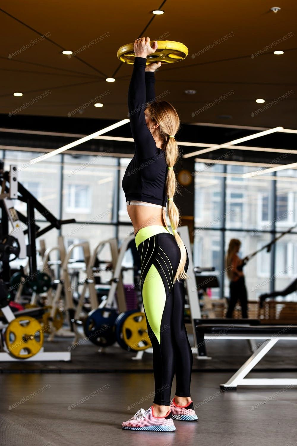girl with long blond hair dressed in sportswear is doing squats with plate in the modern gym By lei