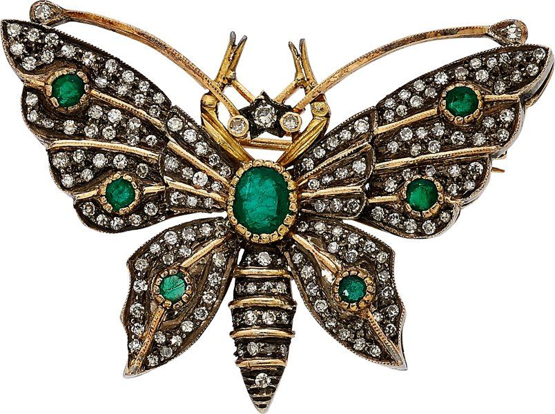 The brooch features round and oval-shaped emeralds weighing a total of approximately 0.65 carat, enhanced by single-cut diamonds weighing a total of approximately 1.25 carats, set in 18k gold and silver. Gross weight 13.30 grams. Dimensions: 1-3/4 inches x 1-3/8 inches Estimate: $2,000 - $3,000.