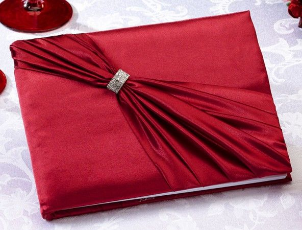 """Red Sash Guest Book This elegant red satin guest book is decorated on the front with a red satin sash and rhinestone ornament. The book measures 8.5"""" x 6"""" and holds 55 pages for a total of 990 signatures. A matching pen set is sold separately. Also available in black and ivory"""